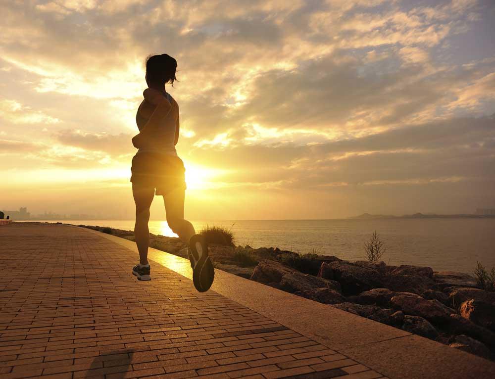 Woman running towards sunrise